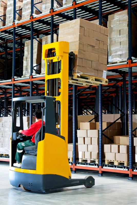 A man operates a forklift to place inventory in a warehouse.