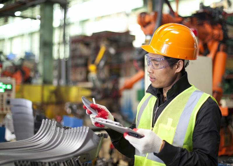 A technician reviews information on a clip board.