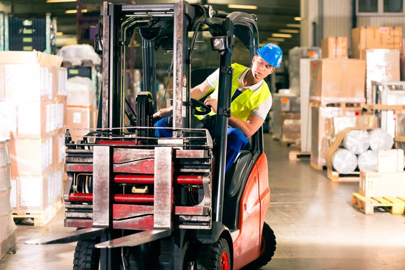 A man leans out of his forklift to look at the path ahead.