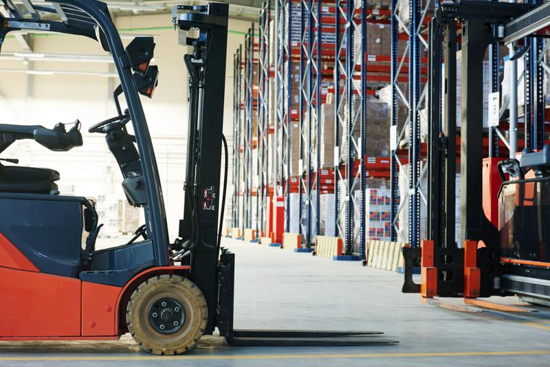 A forklift with lights stands in a warehouse aisle.